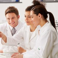 Group Of Scientists Checking Laboratory Results On Computer